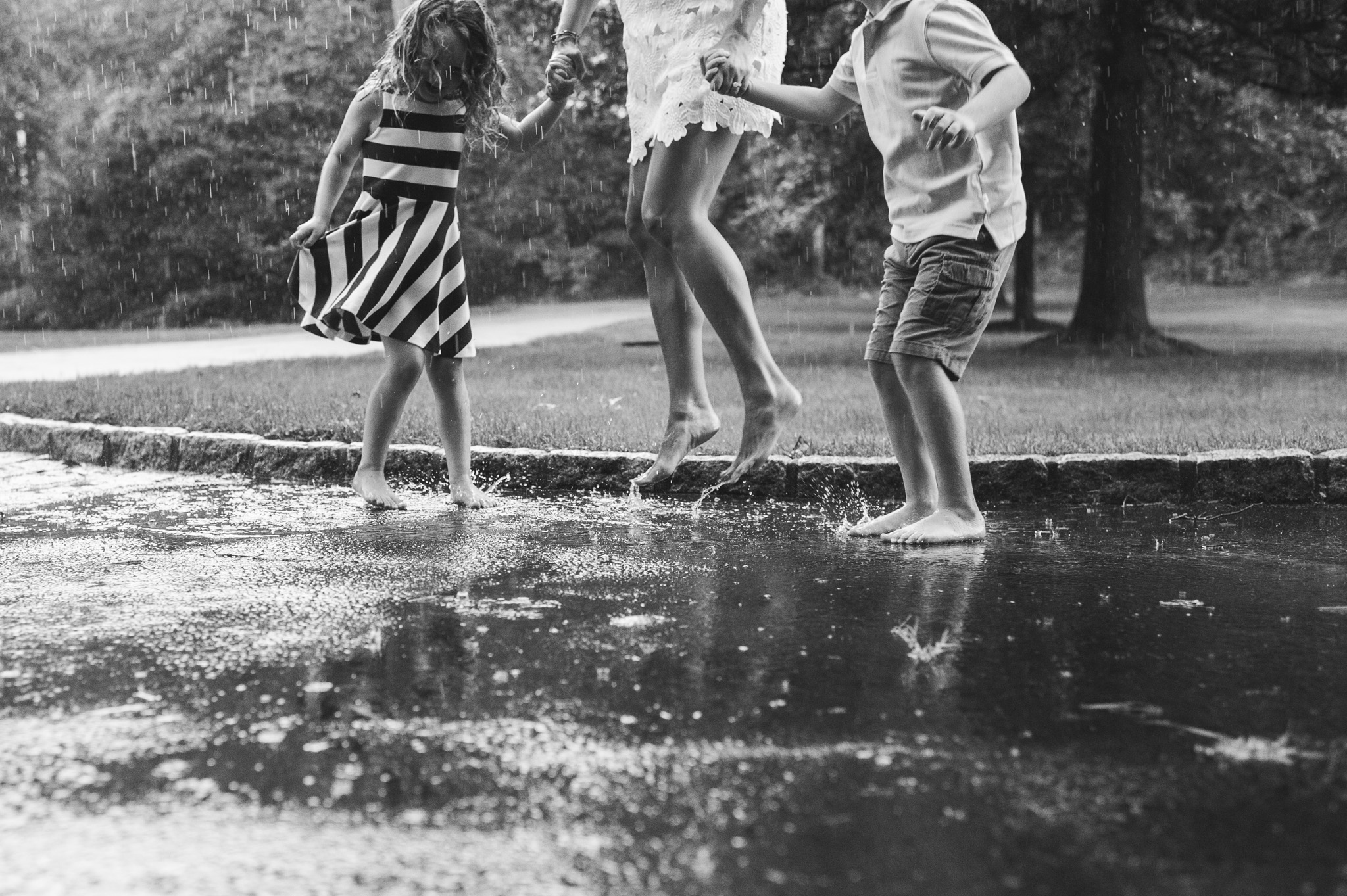 mother and kids jumping in puddles by Erin Borzellino Westchester County portrait photographer