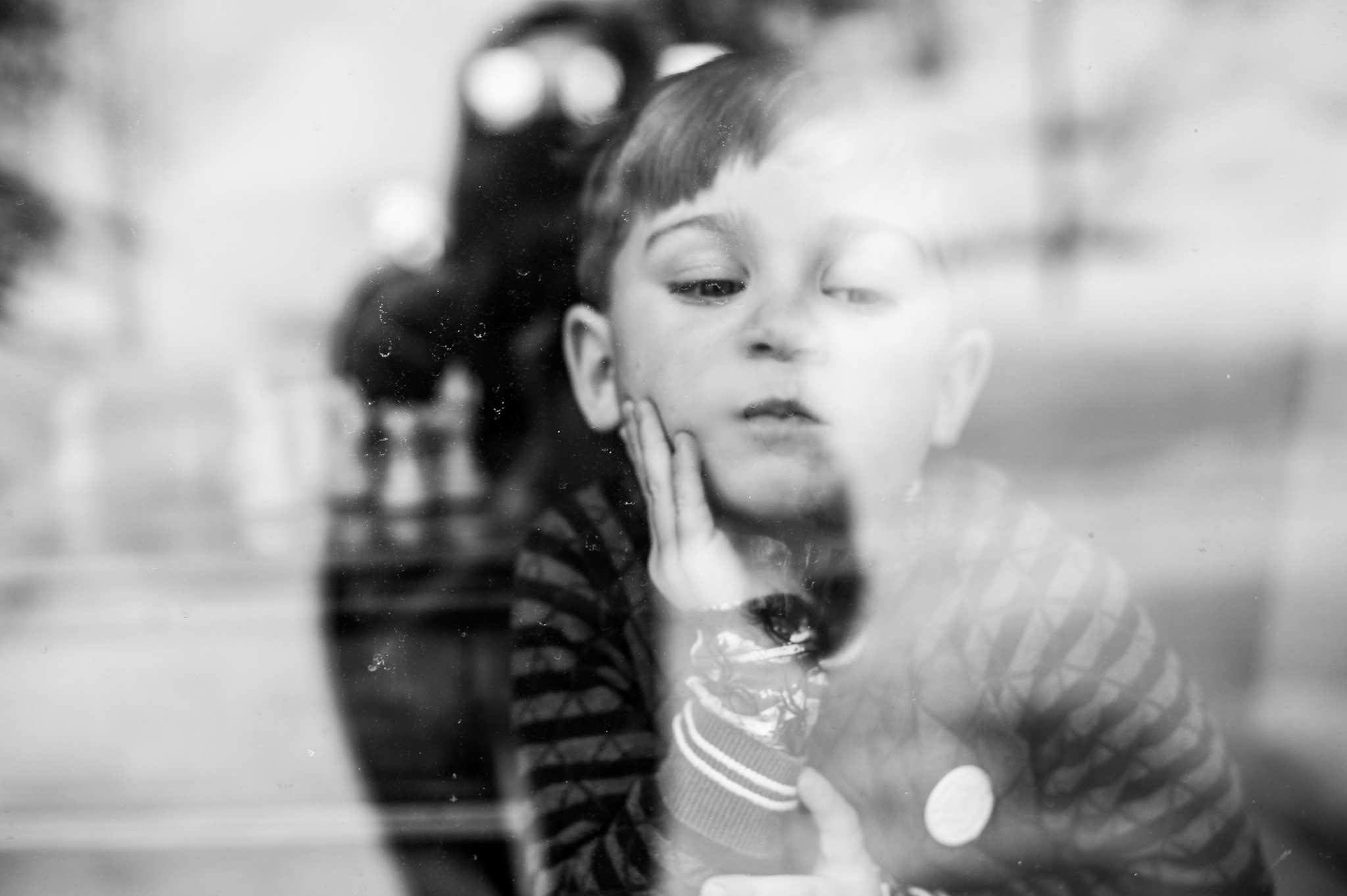 reflection of boy through window.  Portrait by Erin Borzellino. Colorado